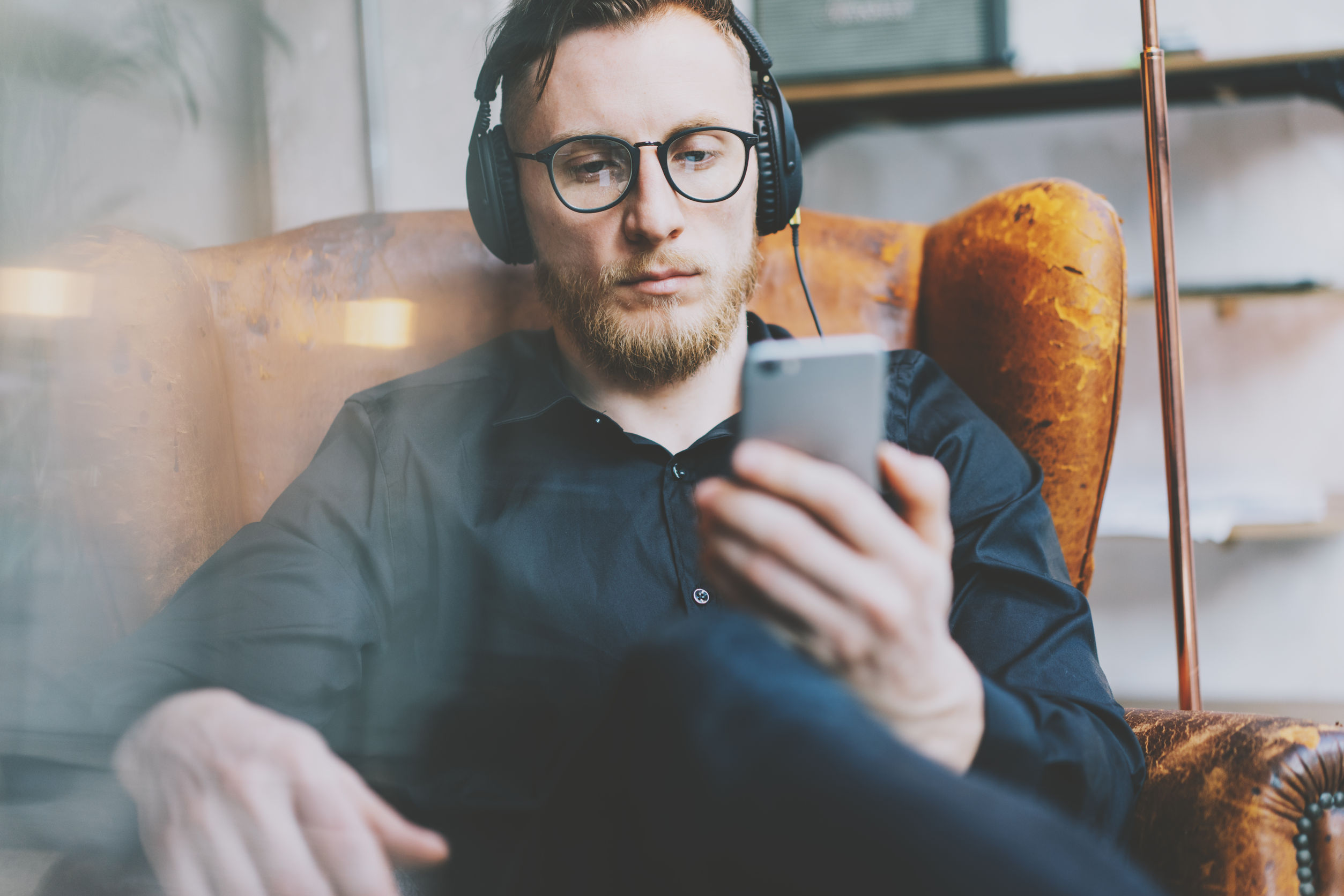 54433004 - closeup photo handsome bearded man in headphones listening to music modern loft studio. man sitting in vintage chair, holding smartphone and relaxing. panoramic windows background, film effect.