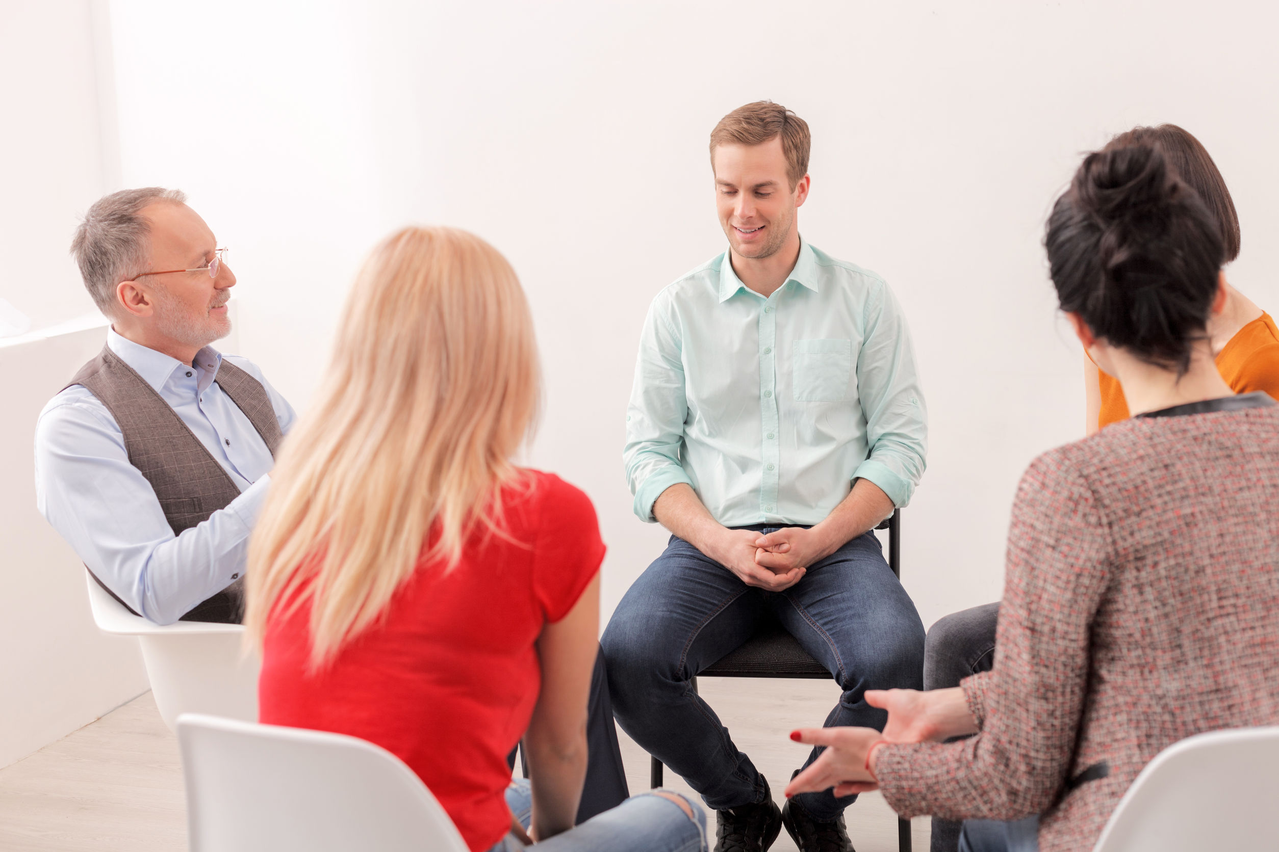 57363091 - attractive young man is sharing his feelings with psychologist and group. he is sitting and smiling. women are listening with joy